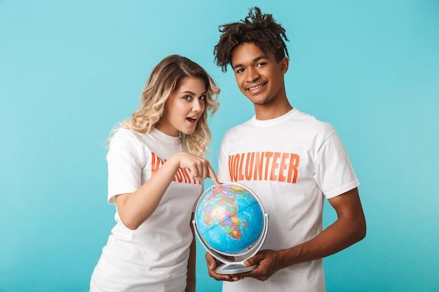 Heureux couple multiethnique confiant portant des volontaires t-shirt isolé sur mur bleu, tenant un globe