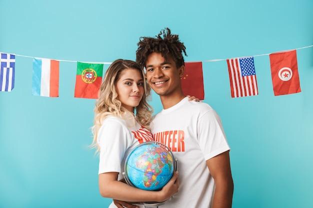 Heureux couple multiethnique confiant portant des volontaires t-shirt isolé sur mur bleu
