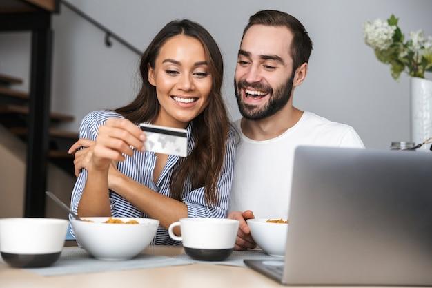 Heureux couple multiethnique prenant son petit déjeuner dans la cuisine, regardant un ordinateur portable, montrant la carte de crédit