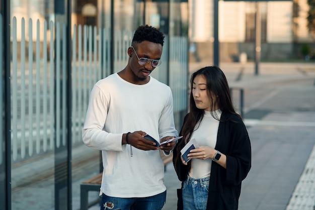 Heureux couple multiracial regarde la carte d'embarquement vérifier l'heure de départ à l'arrêt près de l'aéroport. concept de voyage de vacances.
