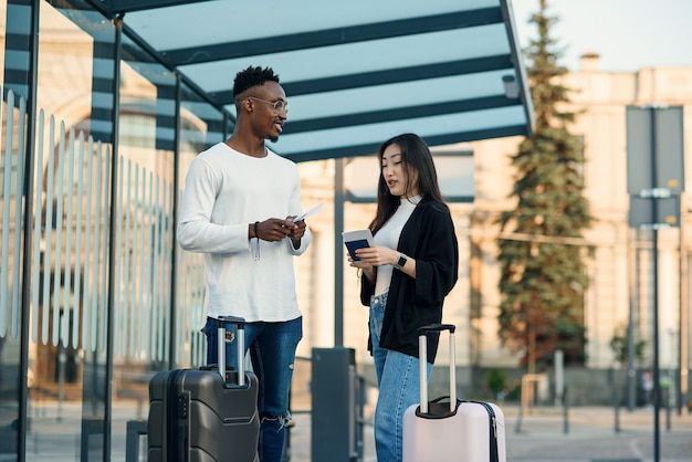 Heureux couple multiracial regarde la carte d'embarquement vérifier l'heure de départ à l'arrêt près de l'aéroport.