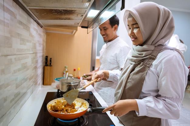 Heureux couple musulman cuisiner ensemble dans la cuisine. homme et femme préparant pour le dîner