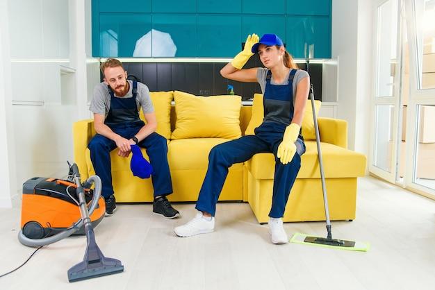 Heureux couple de nettoyeurs professionnels se reposant dans le canapé après avoir nettoyé la cuisine.