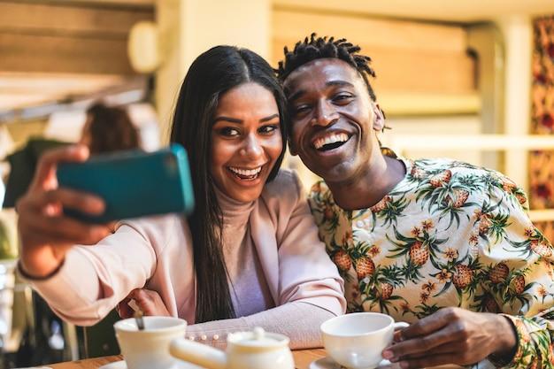 Heureux couple noir buvant du café à l'intérieur de la boulangerie tout en prenant selfie avec téléphone mobile