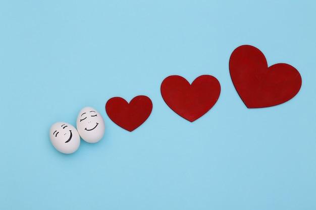 Heureux couple d'oeufs de poule face avec des coeurs sur fond bleu