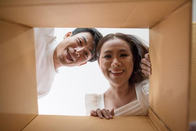 Heureux couple ouvrant une boîte et regardant à l'intérieur du produit