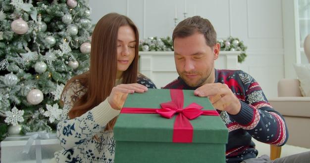 Heureux couple ouvrant des boîtes cadeaux magiques près de noël