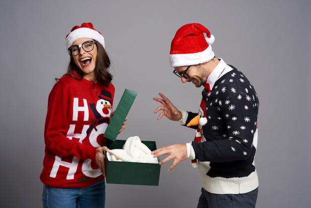 Heureux couple ouvrant le cadeau de noël