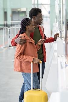 Heureux couple avec passeports étrangers et cartes d'embarquement debout au comptoir d'enregistrement de l'aéroport