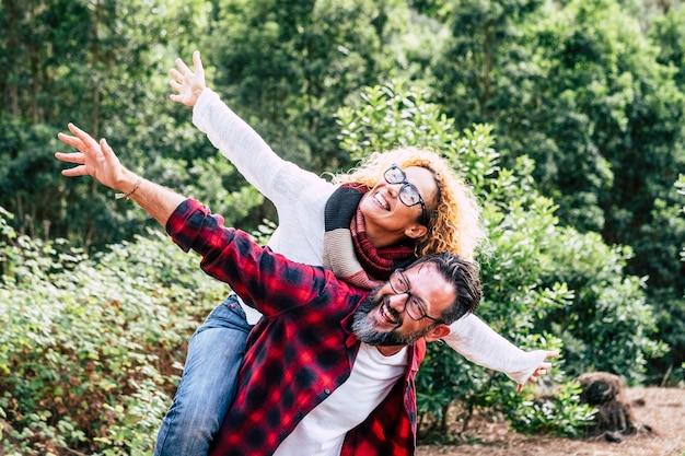 Heureux couple de personnes adultes, homme et femme de race blanche s'amusent ensemble dans une activité de loisirs en plein air dans la nature-environnement et concept d'amour ou de forêt avec un voyageur ludique et jeune