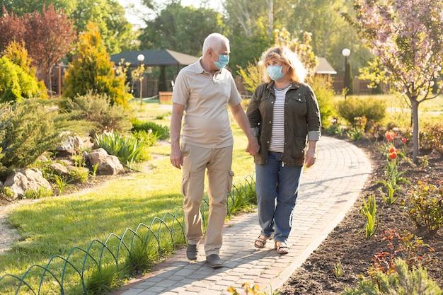 Heureux couple de personnes âgées âgées portant un masque médical pour se protéger du coronavirus dans le parc d'été