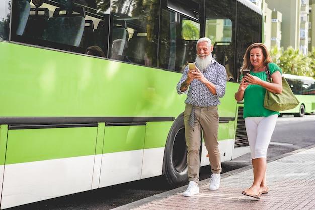 Heureux couple de personnes âgées à l'aide de smartphones à la gare routière