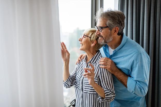Heureux couple de personnes âgées amoureux étreignant et créant des liens avec de vraies émotions à la maison