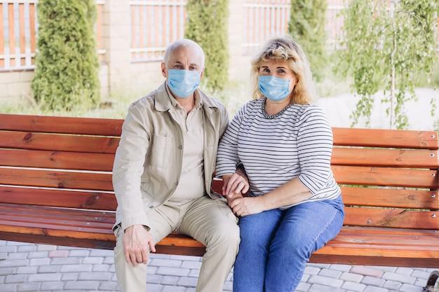 Heureux couple de personnes âgées amoureux portant un masque médical pour se protéger du coronavirus. parc extérieur, mise en quarantaine des coronavirus