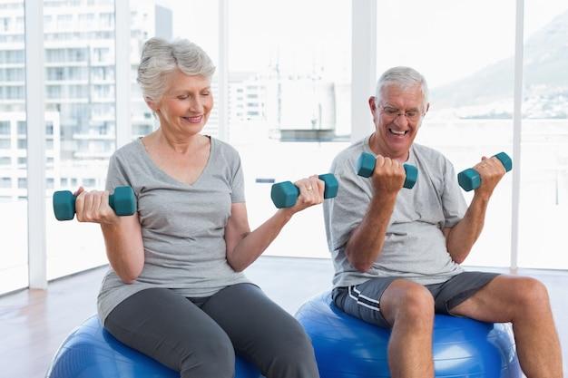 Heureux couple de personnes âgées assis sur des ballons de fitness avec haltères
