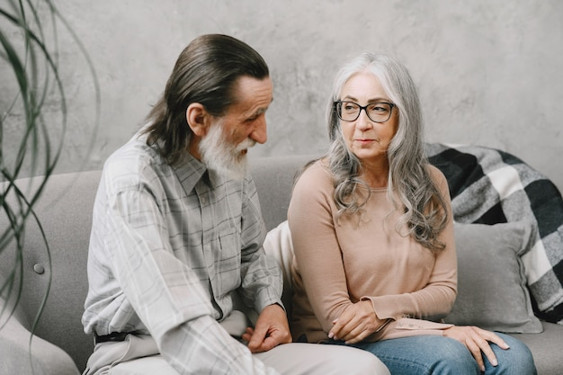Heureux couple de personnes âgées assis sur un canapé à la maison et parlant. concept de temps de qualité.