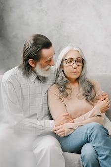 Heureux couple de personnes âgées assis sur un canapé à la maison et parlant