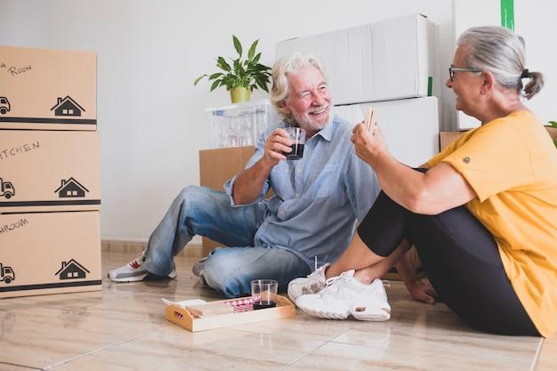 Heureux couple de personnes âgées assises par terre faisant une pause avec de la nourriture et des boissons dans la nouvelle maison pour un nouveau départ comme à la retraite avec des cartons de déménagement sur le sol