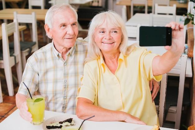 Heureux couple de personnes âgées au café prenant selfie