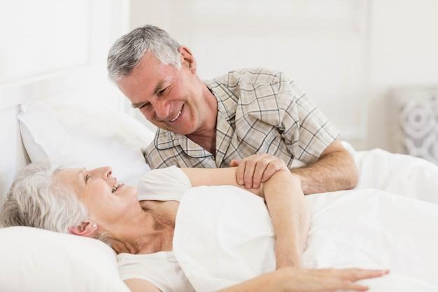 Heureux couple de personnes âgées au lit à la maison