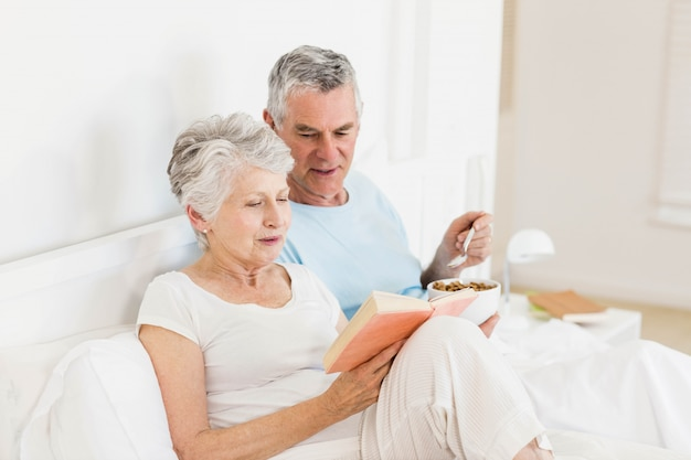 Heureux couple de personnes âgées au lit manger des céréales et livre de lecture