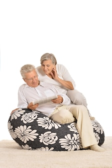 Heureux couple de personnes âgées au repos, assis sur une chaise et lisant le journal