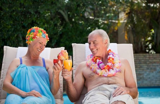 Heureux couple de personnes âgées buvant des cocktails