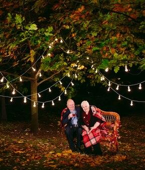 Heureux couple de personnes âgées buvant du thé le soir assis sur le canapé.