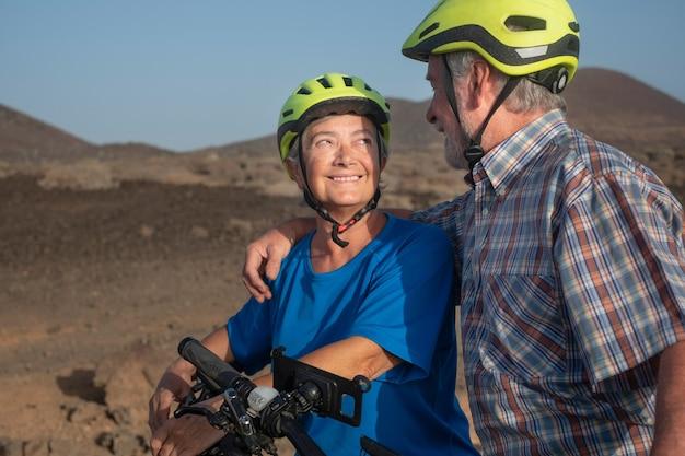 Heureux couple de personnes âgées avec un casque jaune profitant d'une randonnée en plein air avec leurs vélos. concept d'activité et de mode de vie sain