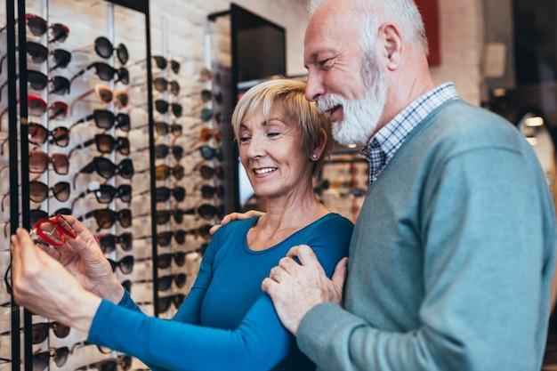 Heureux couple de personnes âgées choisissant ensemble une monture de lunettes dans un magasin d'optique.