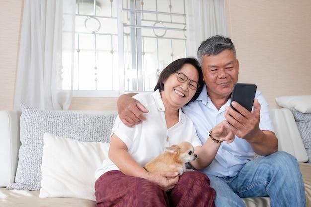 Heureux couple de personnes âgées communiquant en ligne avec la famille via un téléphone portable.
