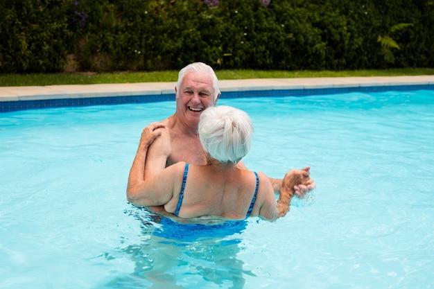 Heureux couple de personnes âgées dansant dans la piscine