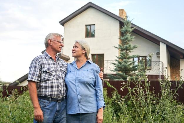 Heureux couple de personnes âgées étreignant et souriant dans le contexte de leur nouvelle maison de campagne