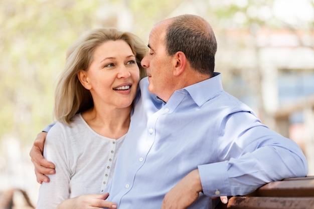 Heureux couple de personnes âgées étreindre sur un banc