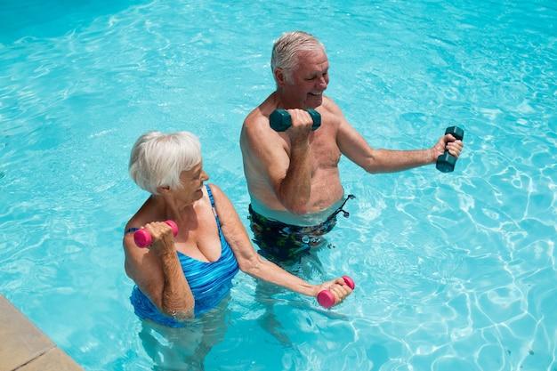 Heureux couple de personnes âgées exerçant avec des haltères dans la piscine
