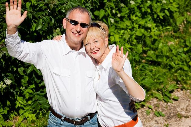 Heureux couple de personnes âgées à l'extérieur en agitant les mains