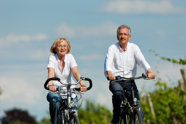 Heureux couple de personnes âgées faisant du vélo à l'extérieur en été