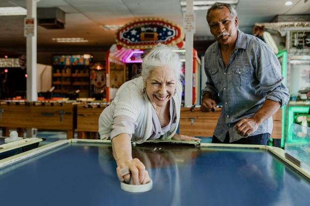 Heureux couple de personnes âgées jouant au hockey sur table à l'intérieur d'une salle de jeux électroniques