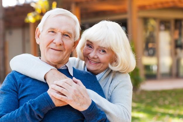 Heureux couple de personnes âgées. joyeux couple de personnes âgées se liant les uns aux autres et souriant tout en se tenant à l'extérieur et devant leur maison
