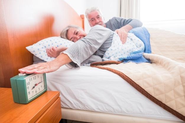 Heureux couple de personnes âgées à la maison arrêter l'alarme au réveil du matin