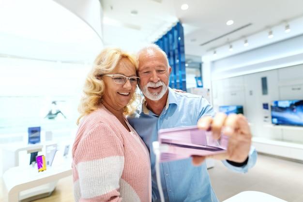 Heureux couple de personnes âgées mariées prenant selfie avec un téléphone intelligent qu'ils veulent acheter. intérieur du magasin tech.