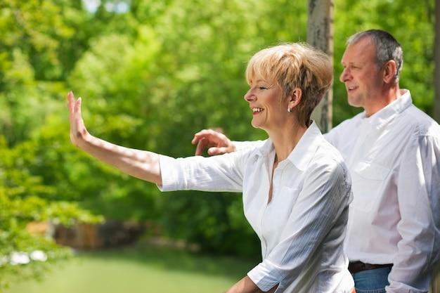 Heureux couple de personnes âgées sur le pont en agitant les mains