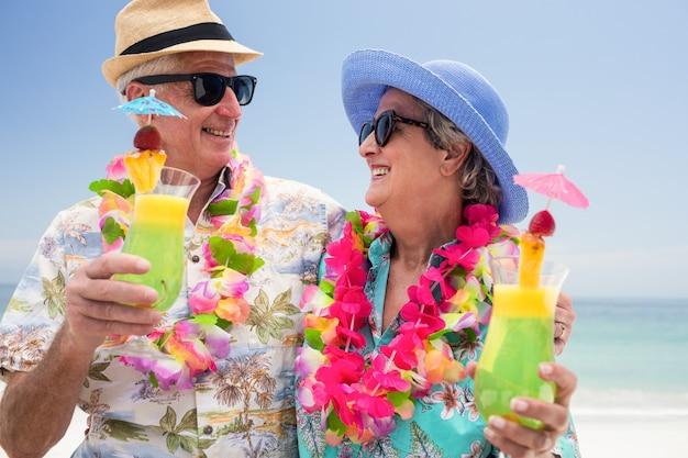 Heureux couple de personnes âgées portant une guirlande et tenant un verre à cocktail
