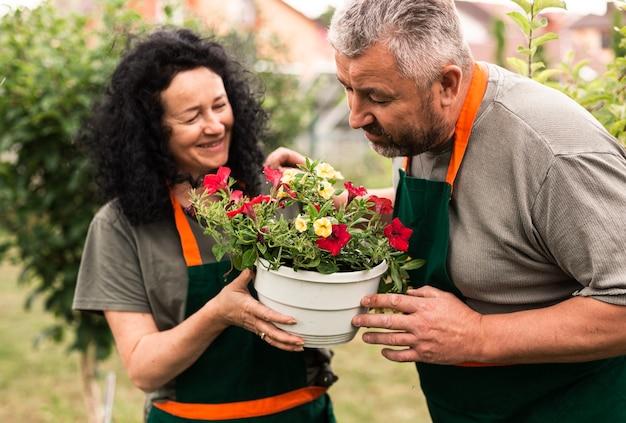Heureux couple de personnes âgées avec un pot de fleur