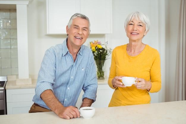 Heureux couple de personnes âgées prenant un café dans la cuisine