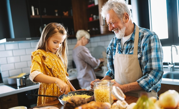 Heureux couple de personnes âgées prenant le petit déjeuner avec leurs petits-enfants à la maison