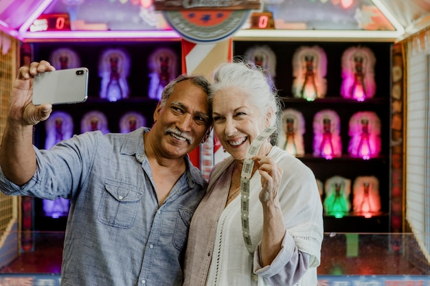 Heureux couple de personnes âgées prenant un selfie avec des billets de tombola