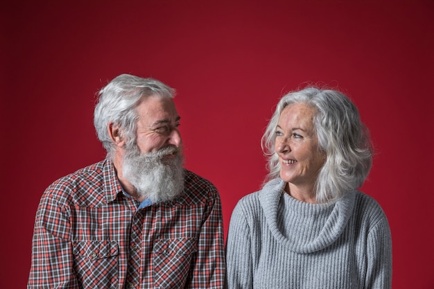 Heureux couple de personnes âgées à la recherche de l'autre sur fond rouge