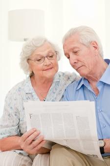 Heureux couple de personnes âgées relaxantes lisant le journal ensemble à la maison