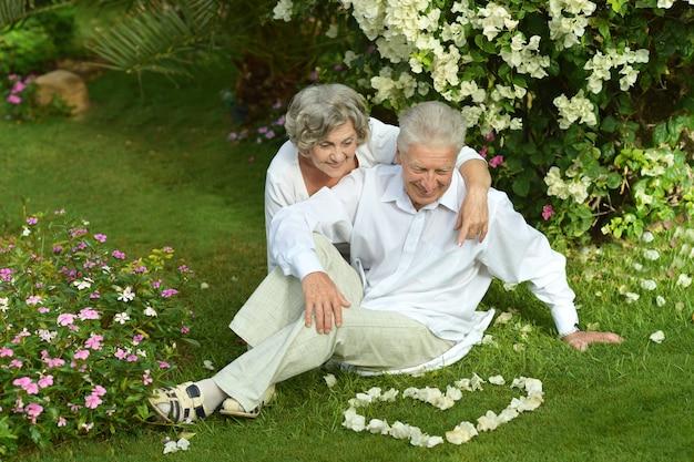 Heureux couple de personnes âgées reposant sur l'herbe sur la nature